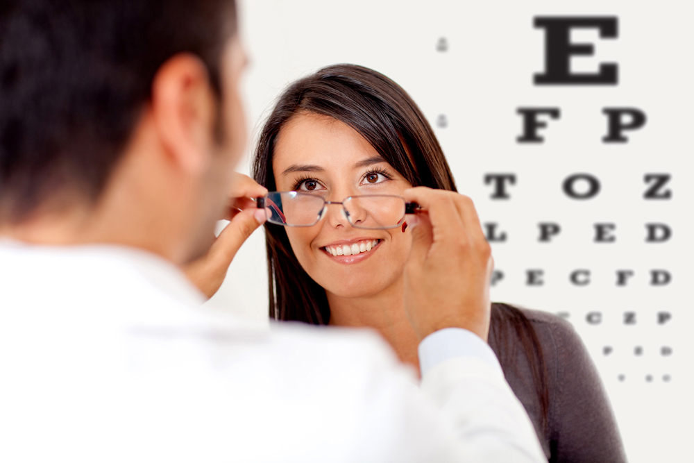 optometrist fitting glasses on woman